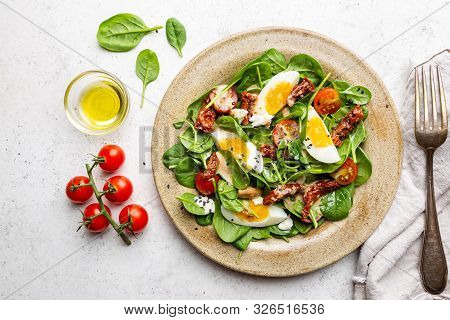 Salad With Spinach, Sun-dried Tomatoes And Eggs. Healthy Home Made Food. Concept For A Tasty And Hea