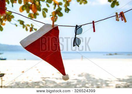 Santa Claus Hat On Caribbean Beach. Beautiful Caribbean Sea And Blue Sky . Christmas Background.