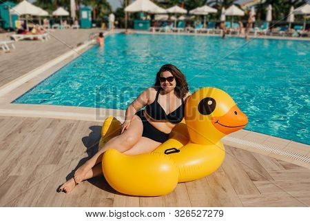 Attractive Busty Curvy Woman In Sunglasses And Black Swimsuit Resting By The Pool With Yellow Inflat