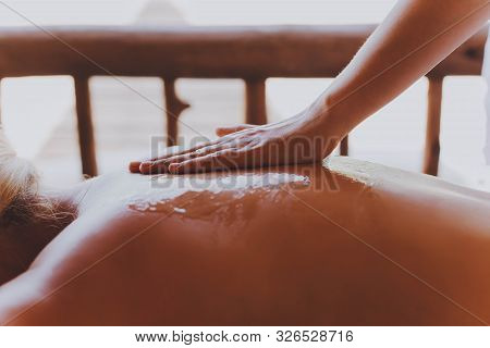 Woman Receiving A Back Massage With Honey In A Spa Center. Female Patient Is Receiving Treatment By