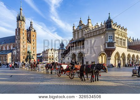 Krakow, Poland - Oct 7, 2014: Horse Carriages In Front Of Mariacki Church On Main Square Of Krakow C