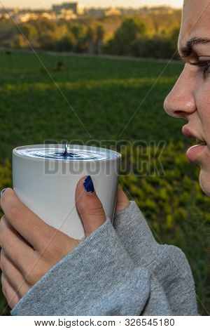 Water Drop Column Rising Out Of Her Drinking Mug Elicits A Scowl Expression From The Female Teen Hol