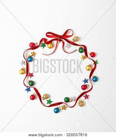 Christmas composition  with red ribbon and Christmas ornaments in shape of Christmas bauble on white background. Merry christmas greeting card with empty space for holiday text. Flat lay