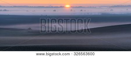 Sunrise Over Fields Reminiscent Of The Italian Tuscan Landscape On A Beautiful Foggy Morning