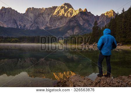 Traveler Admiring The Alpine Lake During Sunrise