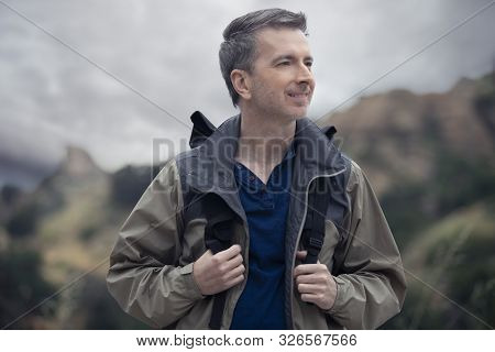Middle-aged Caucasian Male Hiker Trekking Alone In The Mountains. The Overcast Sky Is Peaceful And T