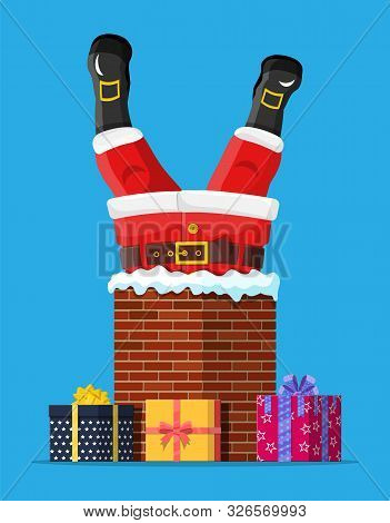 Santa Claus With Gifts Stuck In House Chimney. Happy New Year Decoration. Merry Christmas Eve Holida