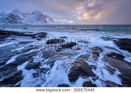Beach of Norwegian sea on rocky coast in fjord on sunset in winter. Vareid beach, Lofoten islands, Norway