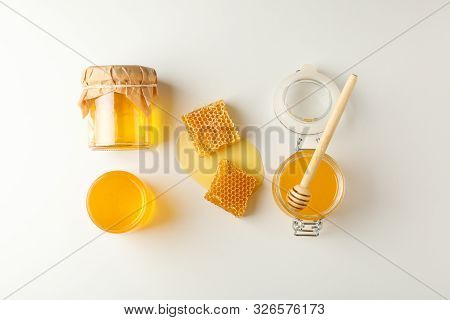 Flat Lay. Jars With Honey, Dipper And Honeycomb On White Background