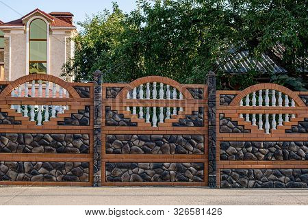 Brown Decorative Stone Fence With Baluster. Against The House.