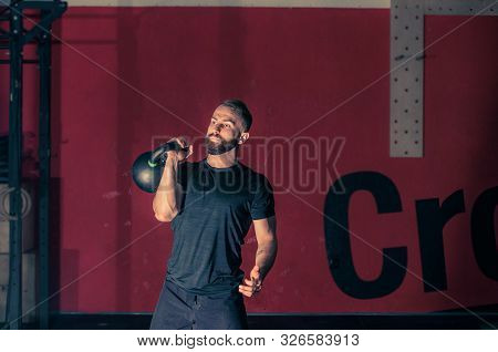 Young Bearded Athletic Man Is Training Pushing A Kettlebell In A Modern Gym. Workout With Kettlebell