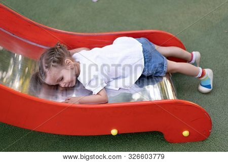Little Caucasian Girl Lies On A Slide At The Playground Tired Of A Sad Summer Day. Chilhood. Tired C