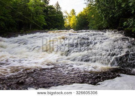 Rushing River From Spring Snow Melt At Bond Falls In The Upper Peninsula Of Michigan.