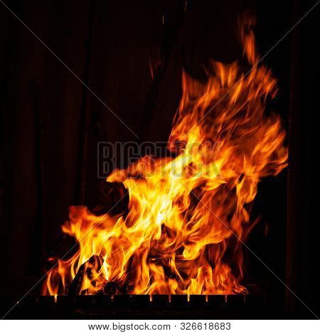 Fire Flame On A Dark Background. Fire Burning At Night. A Fire In The Grill, Fireplace And Hearth. B