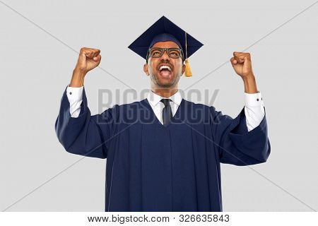 education, graduation and people concept - happy smiling indian male graduate student in mortar board and bachelor gown celebrating success over grey background