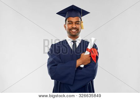 education, graduation and people concept - happy smiling indian male graduate student in mortar board and bachelor gown with diploma over grey background