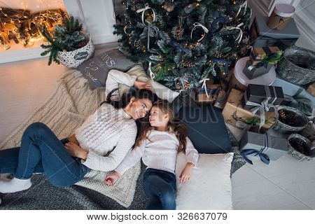 Happy Mother And Daughter Opening Christmas Gifts. Family Gathered Around A Tree At Home. Christmas