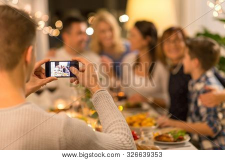 celebration, holidays and people concept - man with smartphone taking picture of family at dinner party