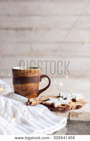 Mug Of Hot Steamy Tea, Christmas Gingerbread Cookies At Wooden Background With Glares. Cozy Morning