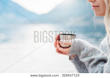 Woman With Mug Of Hot Steamy Beverage By Winter Sea, Blue Mountains. Cozy Picnic With Thermos Of Tea