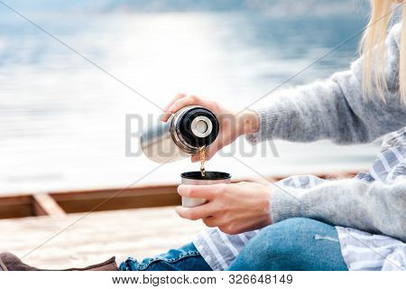 Woman Is Pouring Tea From Thermos Into Mug. Cozy Winter Picnic On Wooden Pier By Sea, Blue Mountains