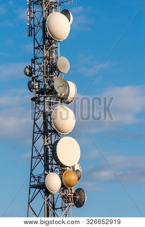 Telecommunications Tower, Antenna And Satellite Dish With Blue Sky On Background.