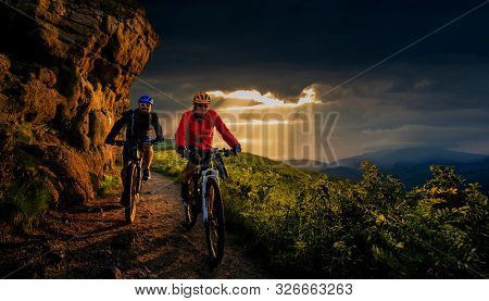 Cycling, mountain biker couple on epic cycle trail in autumn forest. Mountain biking in autumn landscape forest. Man and woman cycling MTB flow uphill trail.