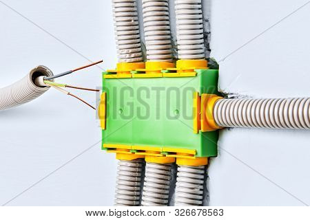 A Flexible Plastic Electrical Conduit Is Connected To The Junction Box Of The Household Wiring Syste