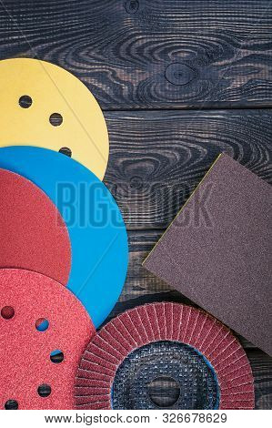 Set of abrasive tools different colors and sandpaper on black vintage wooden background. The wizard is used for grinding items poster