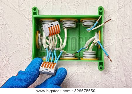 Installation of a junction box in a home electricity system without using a ground wire. Electric connector with spring and lever used for splicing electrical wires. poster