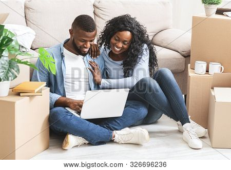 Just Married Young African Couple Sitting On Floor At New House, Shopping Online, Using Laptop, Empt