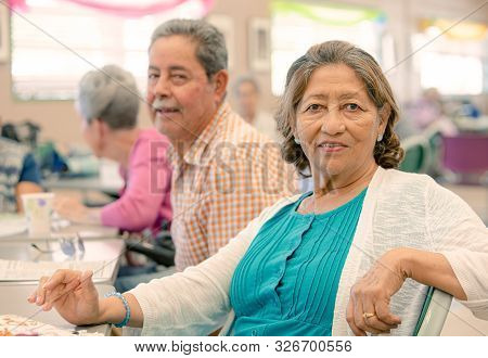 Mature Hispanic Woman In A Busy Senior Center