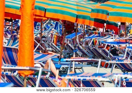 Monterosso Al Mare, Italy - September 02, 2019: Many Striped Blue, Red, White Deckchairs, Sun Umbrel