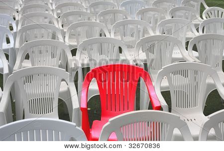 One red chair among many white plastic chairs. Special or reserved seating. poster