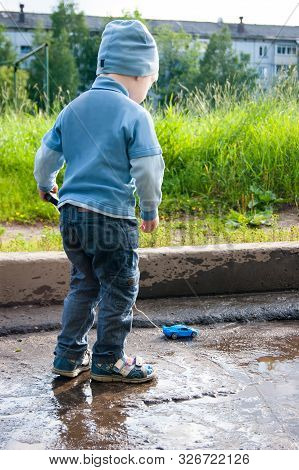 A Three-year-old White Boy In A Blue Hat, Jeans And Sandals Plays On A Cool Summer Day With An Outda