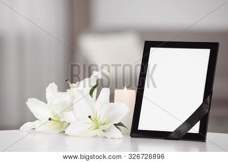 Funeral Photo Frame With Black Ribbon And Lilies On White Table Indoors. Space For Design