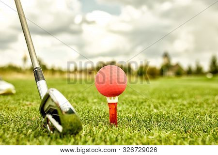 The Ball At The Hole On The Golf Course. Golf Concept. Closeup Of A Golf Ball On Green Grass Next To
