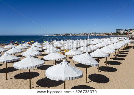 Cascais - August 14, 2019: Rows Of White Umbrellas At The Concessioned Beach Of Tamariz Beach, In Es