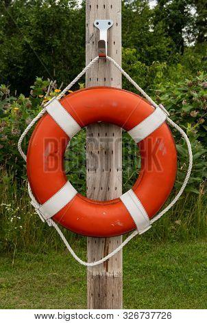 Single Orange Life Preserver On Post Along Shore Of Lake