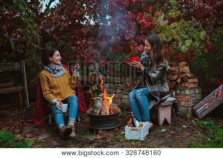 Two Friends Relax Comfortably And Drink Wine On An Autumn Evening In The Open Air By The Fire In The