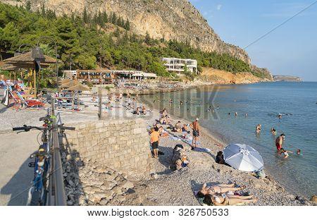 Beachgoers At Arvanitia Beach In Greece.
