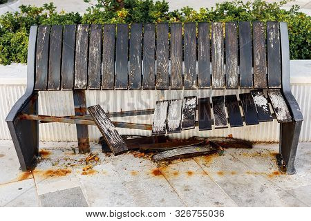 Damaged And Broken Wooden Brown Bench On The Street, Aging Or Vandalism Concept