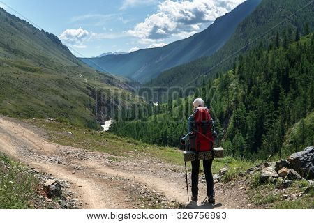A Girl With A Backpack Walks Along A Trail Along A Mountain River. Background For Outdoor Travel.