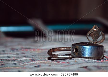 The Old Lock And Key On Abed Of Clothes With Blur And Black Background