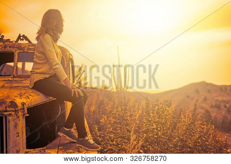 Woman Sitting On Rusty Old Classic Truck. A Woman Admires The Sunset On An Autumn Field.