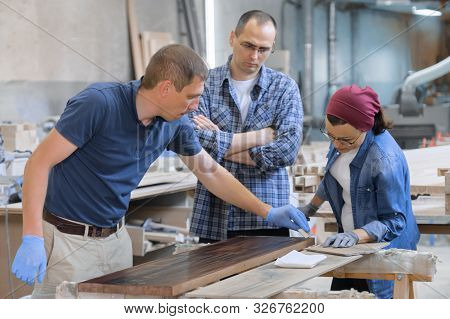 Workers in carpentry woodworking workshop, varnishing wooden plank with oil. poster