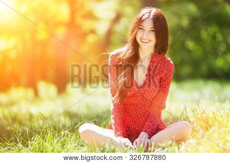 Young cute woman in red dress relaxing in the park. Beauty nature scene with colorful background, trees at summer season. Outdoor lifestyle. Happy smiling woman sitting on green grass