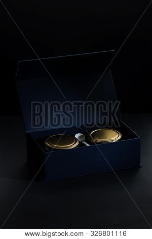Black Sturgeon Caviar On A Spoon. Glass Jars With Black Sturgeon Caviar - An Expensive Gift Set In A