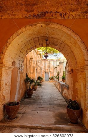 Great Design Of Passage Between The Houses In Greece Decorated With Flower Pots Everywhere. Old Wall