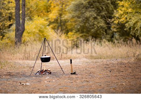 Campfire With Camping Tools Such As Axe And Hanging Pot Over Fire. Secluded Relaxation In Autumn For